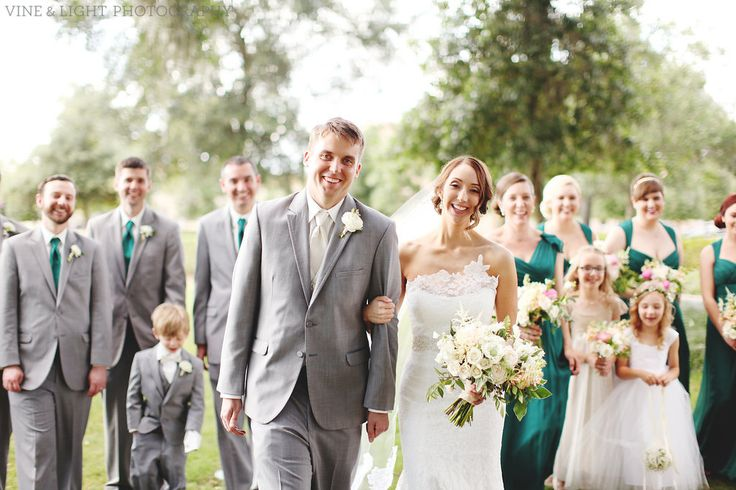 a delighted wedding party of groomsmen in grey suits and bridesmaids in emerald green gowns head off to the reception.