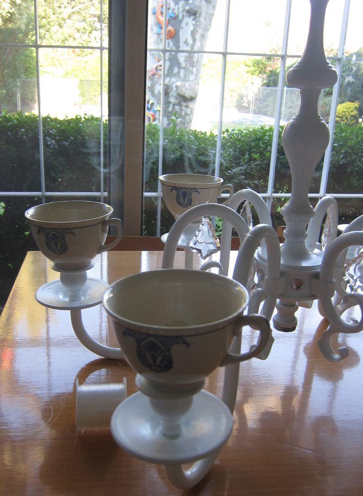 Recicladod e una antigua araña de bronce , repintada a blanco y con un juego de tazas inglesas  para sostener veletas en su interior, unos caireles de acrílico y gemas  lo convirtieron  en un centro de mesa.