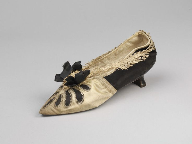 ca. 1790, black and pale yellow satin. Trimmed with a black satin ribbon rosette and a silk tassel at the toe with braid trimming around the top of shoe. Petal cutouts in yellow satin at the toe exposing black beneath. The Louis heel is faced with black leather. The heel quarters are lined with white kid leather and the toes with canvas. There is a canvas inner sole, V&A