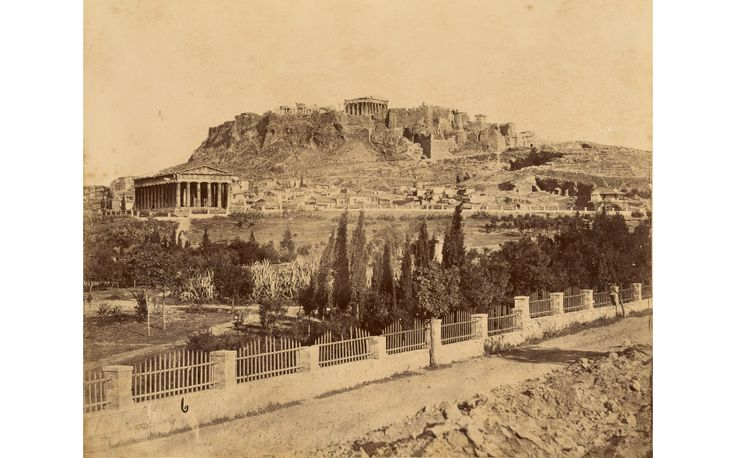 Distant view of the Acropolis seen from a dirt road bordered by a low wall. The ruins of the Acropolis are on top of a hill with a city visible below. The Temple of Hephaestus is in the field between the city and the road. Trees are scattered across the field. Date: about 1865 - 1880. Artist/Maker: Unknown