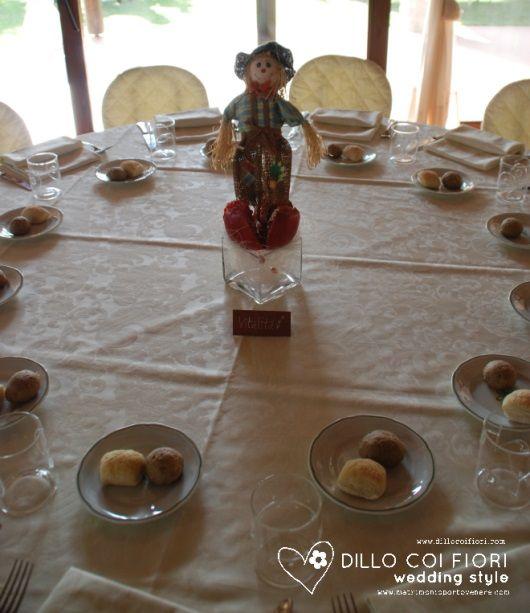 tavolo dei bambini con pupazzo di paglia e melograno