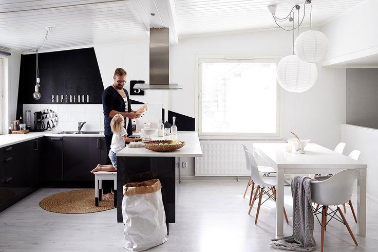 Åpen kjøkkenløsning med sort-hvitt fargepalett og nordisk stil. Vitra Eames Plastic Side Chair DSW, designet av Ray og Charles Eames.