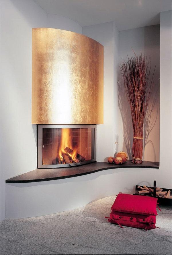 Cheminée d'angle avec hotte dorée, tablette en granit noir finition cuir, foyer Ruegg Ellipse.