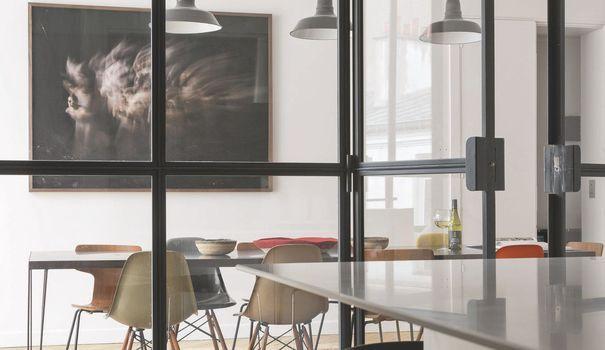 La cuisine avec îlot s'ouvre sur la salle à manger grâce à une verrière qui s'ouvre à l'envi.