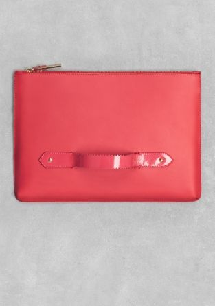 A structured leather clutch featuring a smooth texture and handle for a comfy grip.