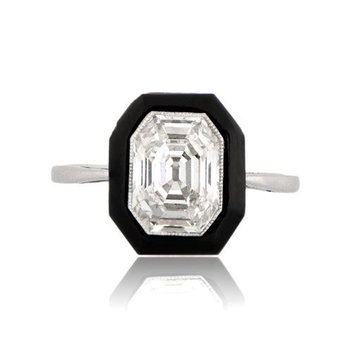 A Majestic Antique Onyx Engagement Ring Set in Handmade Platinum. The center antique emerald cut diamond is bezel set and is surrounded by fine milgrain and a halo of onyx.