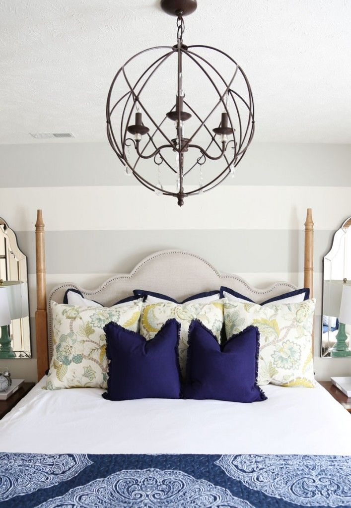 Modern Muse Maison Poster Bed in Guest Bedroom with gray and white striped walls, orb chandelier, blue and white bedding and floral throw pillows.