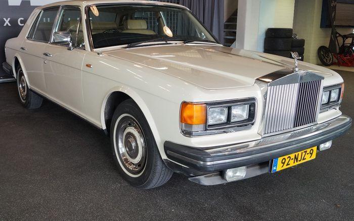 Rolls-Royce - Silver Spirit4-deurs Saloon - 1982  APK: geldig tot 31 mei 2018Kenteken: 92-NJZ-9Bouwjaar: 2-01-1982Tellerstand: 50.303 mijlBrandstof: Benzine (Euro 95 ongelood)Wegenbelasting: 120 euro per jaar in Oldtimertarief (niet mee rijden van 1 december tot 1 maart)Kleur carrosserie: Magnolia WhiteKleur interieur: Vanille-beige Leder met Bruine bies; Bruin tapijt met Lederen Vanille-beige bies; Houtwerk NotenMotor: V-8 6750 CC in goede staat; o.a. nieuwe benzinefilters; nieuwe…