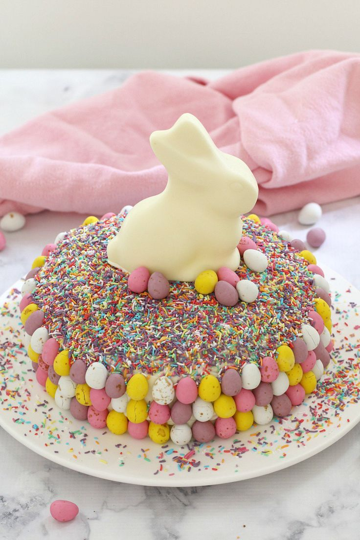 15 minutes is all it takes to whip up this show stopping EASY WHITE CHOCOLATE & MINI EGG EASTER CAKE. It looks AMAZING but is the simplest recipe ever!!! A store-bought white chocolate mud cake covered in white chocolate frosting, heaped with pretty sprinkles and decorated with pastel chocolate Easter eggs and a white chocolate bunny… this really is the ultimate Easter cake!    #easter #cake #lindt #minieggs #recipe #easy #kids