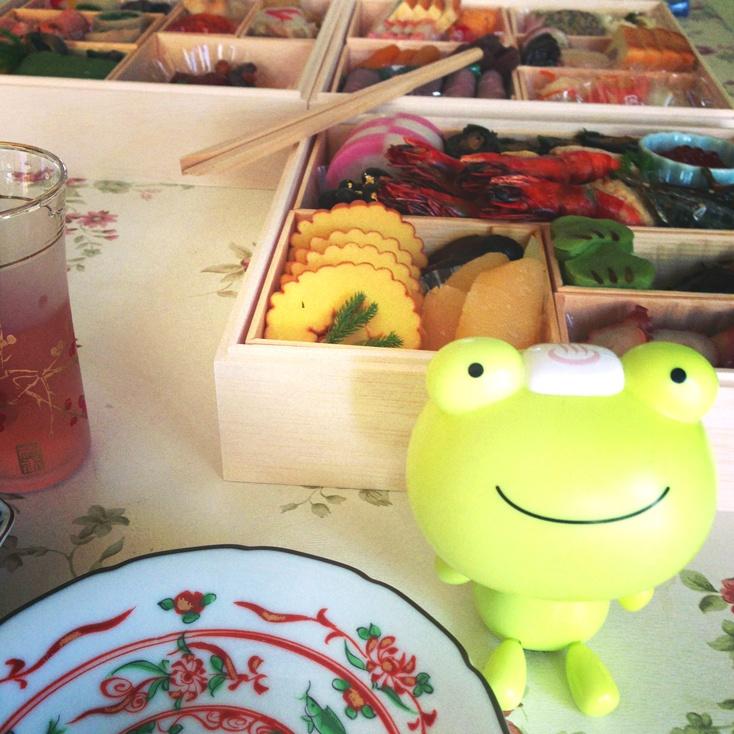 """カエルくんと元旦その2です。  あけましておめでとうございます!  ということでおせちを頂きます。  手前に見える伊達巻きですが、巻物ということで知恵をえられますように、との意味があるそうです。  This is part 2 of New Year's Day with Pukaka Frog.  Happy New Year!  so , we ate """" osechi """"lunchbox .  """"Datemaki""""rolled omlet wecan see in box is a wish that is likely to be obtained as you scroll so wisdom."""