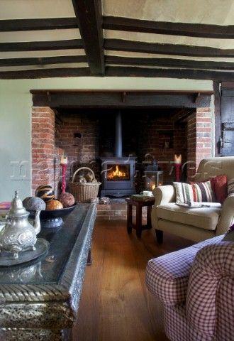 Lit woodburner in brick fireplace in beamed living room