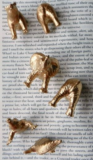 Buy plastic animals from dollar store, cut in half, spray paint gold, and glue magnet on bottom.