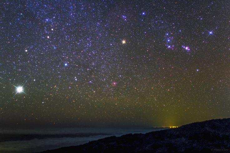 Jupiter glows the brightest in this photo, appearing above the horizon and clouds toward the left. The constellation Orion can be seen above right with its second brightest star, Betelgeuse shining in orange. Miguel Claro took this photo on Jan. 24, 2014 from Los Andenes, La Palma, Canary Islands.
