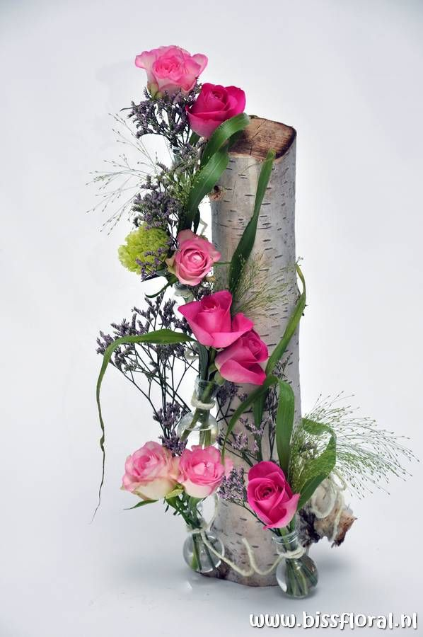 Birch trunk with roses in bulb vases
