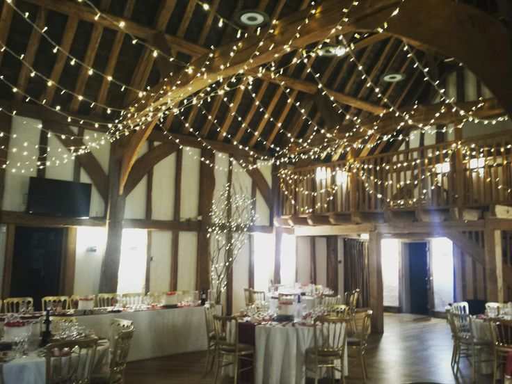 A beautiful fairy light canopy sweeping beam to beam with fairy light swags on the balcony #barnwedding #fairylighting #buckinghamshire #eventprofs #wedding