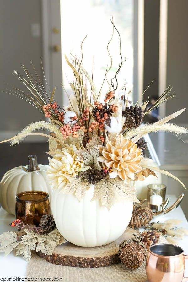 A white faux pumpkin adds fall flair to this centerpiece. The arrangement of pinecones, branches and burlap leaves is both rustic and elegant. Get the tutorial at A Pumpkin And A Princess »