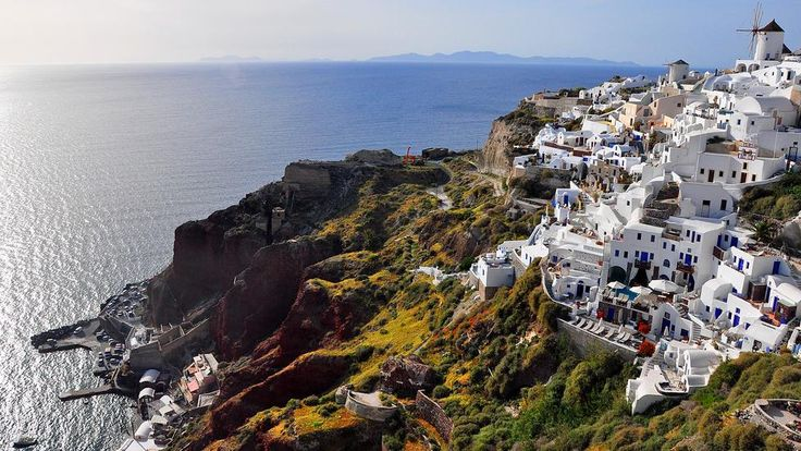 The famous eruption of Santorini's volcano was in 1600BC, creating the caldera as we know it now. 200 times the force of Mt St Helens, the upsurge was felt across the Aegean, sending a 150m-tall tsunami to Crete ending the flourishing Minoan civilization. This view is of the town of Oia. In the foreground, the caldera cliffs show the extraordinary colors of the volcanic rocks and the flora that thrive in the mineral-rich soil.   #santorini #greece #color #oia http://esperas-santorini.com/