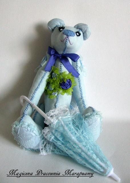 Blue teddy bear with umbrella.