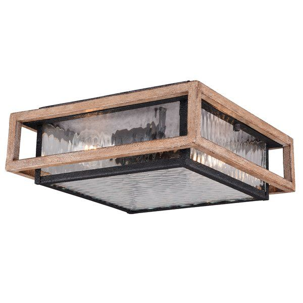 An industrial design with rustic appeal, this charismatic two-light outdoor flush mount illuminates your space in factory-chic style. Featuring a boxy metal frame in a weathered black iron finish, this weather-resistant design showcases rectangular rain glass panels and a tastefully distressed gold outer frame. Establish an understated aesthetic on your back deck by rolling out an all-weather crosshatch area rug for a touch of texture, then place a wrought iron end table with a raw steel…