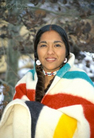 A Young Shoshone woman wraps herself  in a Hudson Bay trade blanket.  For over two centuries the Hudson's Bay Company point blanket has been a familiar item in Canada.  Hudson's Bay Blankets were so important to early trade that they were considered a form of currency.