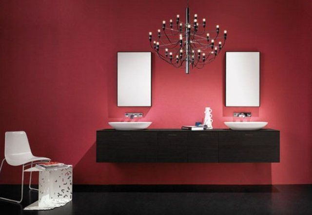 A dark wood floating vanity with vessel sinks stands out against the marsala walls of this modern bathroom.