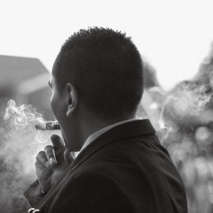 Unieke en eigenzinnige bruidsfotografie Amsterdam. Een rauwe zwart wit foto van een bruidegom die een sigaar rookt tijdens de bruiloft.