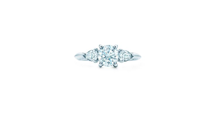 Two pear-shaped Tiffany diamonds bring an air of glamour to this classic round brilliant center stone.