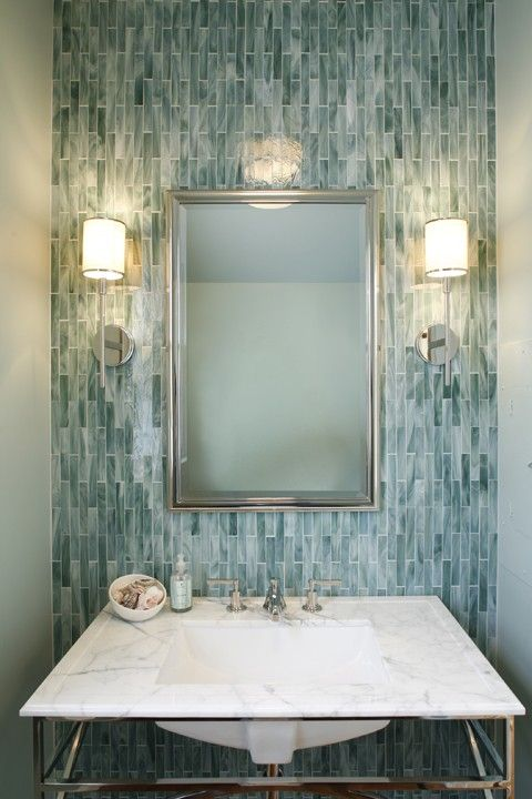 Beautiful powder room design with blue glass tiles backsplash, silver mirror, polished nickel sconces and Calcutta marble washstand with polished nickel legs.