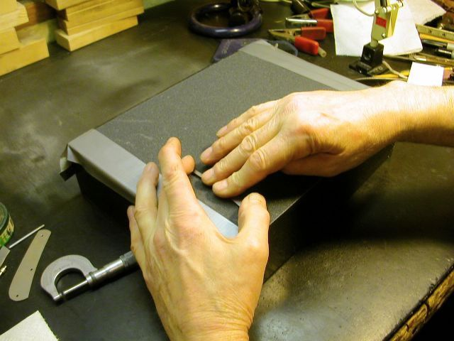 Sand the spring with 180 grit sandpaper taped to a perfectly flat surface, in this example a 9x12 granite bench plate.