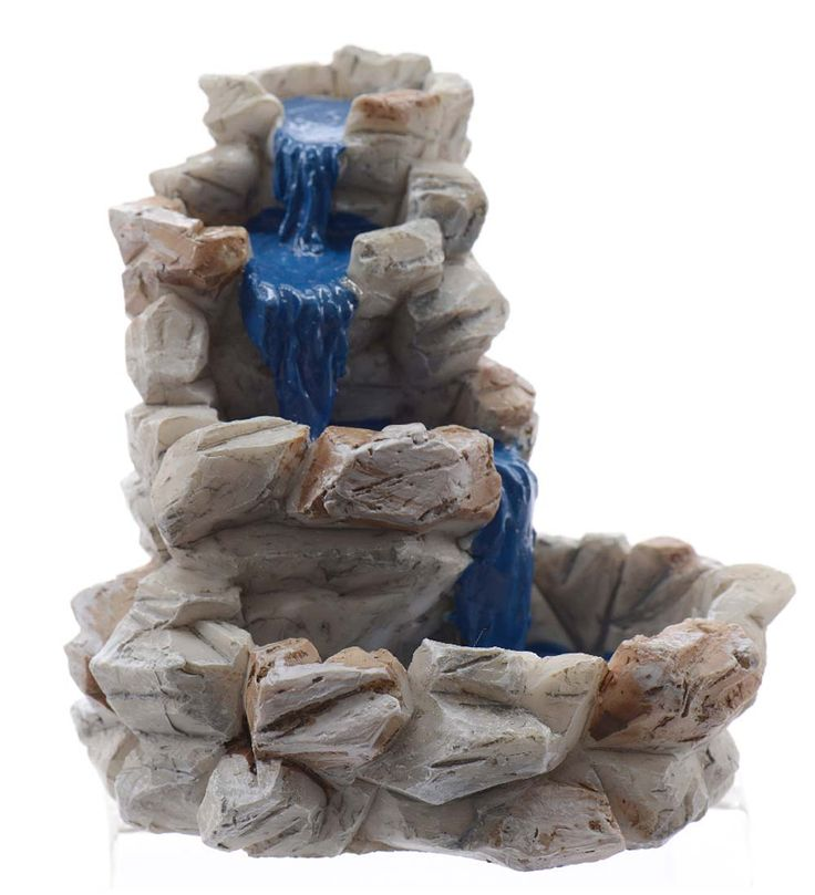 """Miniature fairy stone fountain is crafted of durable poly-resin that's designed to look like warm brownstone and features a stream of blue """"water"""" tumbling down its three stacked tiers."""