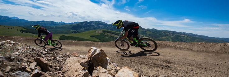 Two downhill mountain bikers going around a berm with the mountains in the background