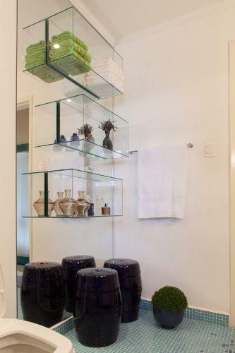 """(...) Para criar unidade, o piso recebeu pastilhas menores em composição """"degradê"""", Destaque para os nichos de vidro colados sobre o espelho, que economizam espaço, embelezam o ambiente e são práticos organizadores"""