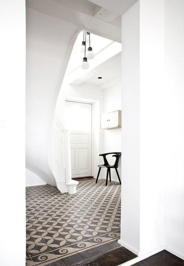 Dramatic hallway with original tiles & lots of white.