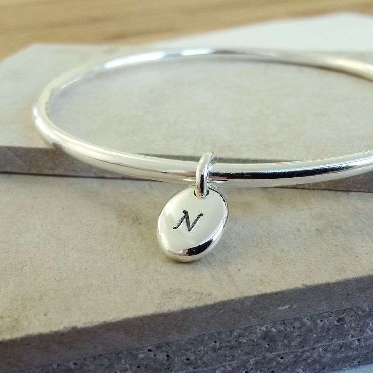 Simple, stylish, personal.  Our solid silver bangle with engraved with your initial to order - handmade in Hove, it's such an easy personalised gift for her.