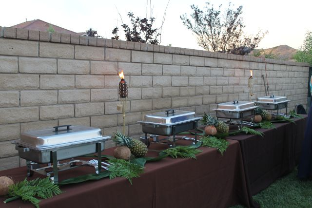 3 8' banquet tables with chocolate brown linens lined up to provide a buffet station to serve Cuban food from Hidden Havana Cafe, located in Newhall, CA. Pineapples, coconuts, and greens to decorate the space. #a1eventrentals