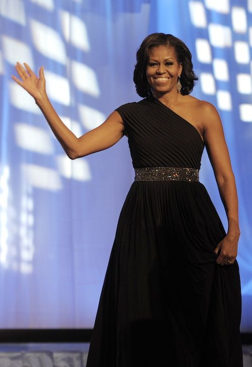 Mrs. Obama is in a Michael Kors black georgette pleated one shoulder gown paired with a pretty rhinestone belt.