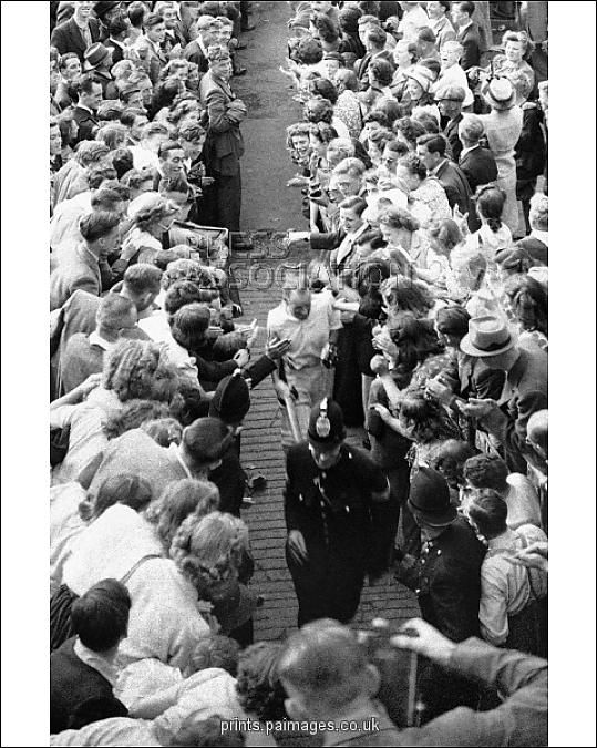 AUSTRALIA'S DON BRADMAN MAKES HIS WAY BACK to the pavilion through crowds of well-wishers after helping his team to victory with an unbeaten 173 on the final day. Australia set a new test record (which stood until 1975) by scoring 404 in their second innings to win the game. Image from PA Photos.
