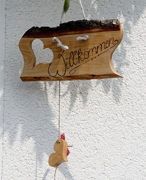 """Das dekorative Türschild aus Holz mit der Aufschrift """"Willkommen"""" eignet sich ideal als einladendes Deko-Element für die Eingangstür Ihres Hauses oder Ihrer Wohnung. Heißen Sie Ihre Gäste willkommen mit unserem wunderschönen Holz-Tüschild für die Wohnung oder auch für den Laden. Unser Schild besteht aus naturbelassenem Holz und ist mir einer Kordel und der Aufschrift """"Willkommen""""."""
