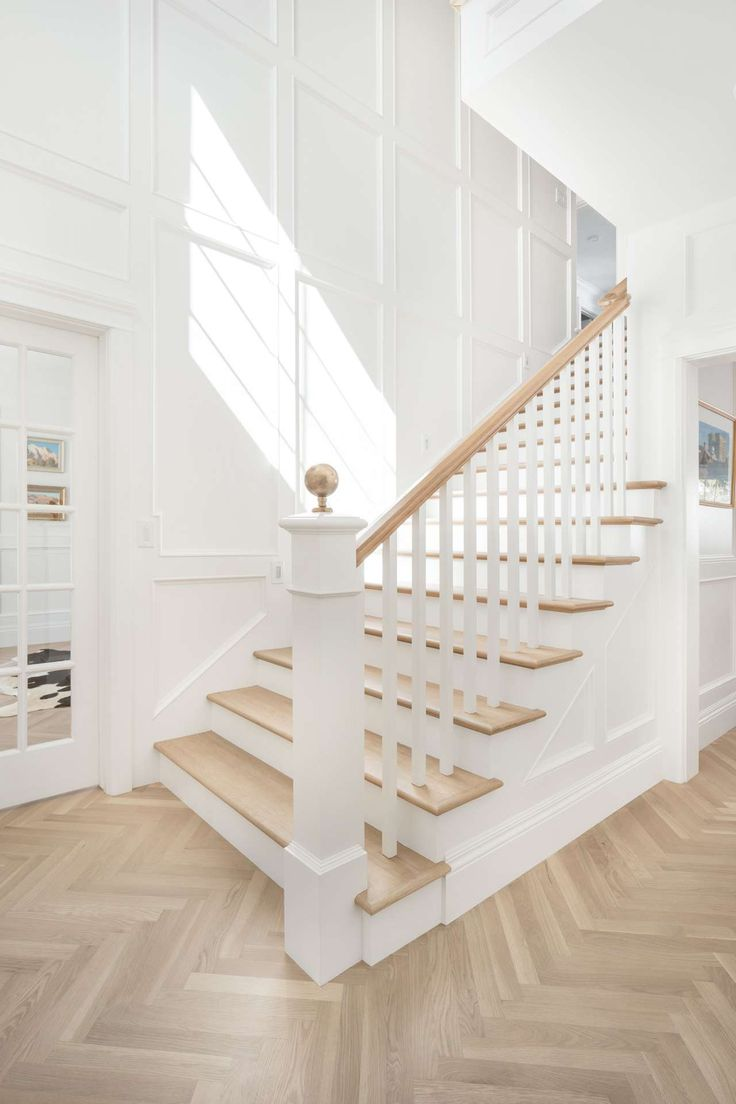 Entry. White English farmhouse style home by The Fox Group. Come be inspired these English Farmhouse Style Decorating Ideas. #staircase #entry #interdesign #benjaminmooresimplywhite