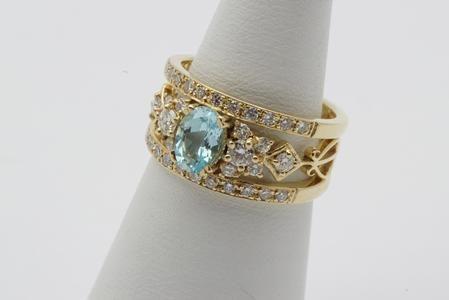 Een 14 krt. bicolore gouden ring met opengewerkte band met o.a. harpmotieven en bezet met een blauwe topaas, 0.90 ct., en vele briljanten, 0.65 ct