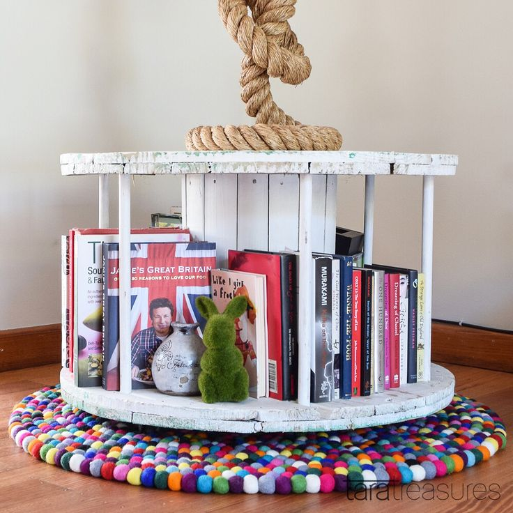We were determined to upcycle as much as we can from mill and flea markets in Melbourne. Hence the bookshelf made from a cable spool, which doubles up as a lamp stand as well. Placed on a handmade felt ball rug from our stall. #feltballrug #taratreasures