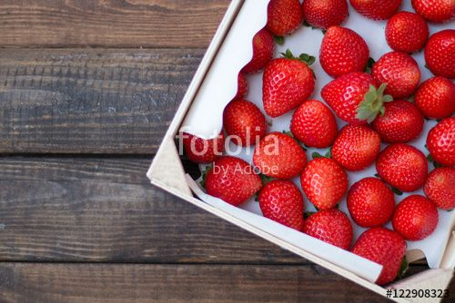 Caja de fresas sobre un fondo de madera
