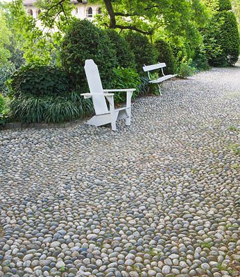 GARDEN OF PAOLO PEJRONE, ITALY: COBBLED PATH WITH WHITE WOODEN FURNITURE.  clivenichols.com