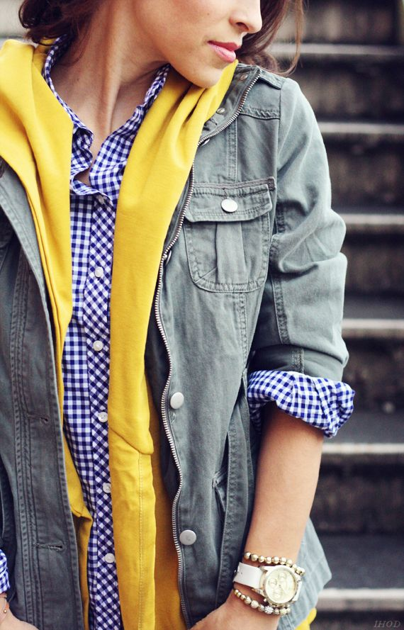 Blue plaid shirt, yellow cardigan or scarf, army green military style jacket.