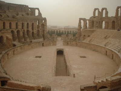"""""""The Amphitheatres of El Jem"""" Today El Jem, or Thysdrus as it was known on Roman times in Tunisia is famous for containing one of the largest Ampitheatres anywhere in the Roman world. It was the third ampitheatre built in the town. The two earlier ones were built some distance away, at first only about 5 to 6,000 people could be entertained when the top of a small hill was hollowed out as an arena but after it was rebuilt this number rose to 7 to 8,000."""