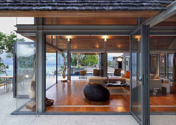 Steel frame and glass. I love how warm this modern house looks