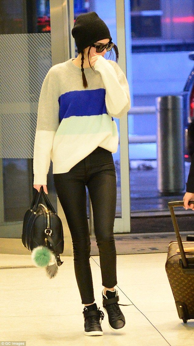 Off-duty model style: Kendall Jenner looked casual cool in a pair of tight skinny jeans, trainers and a loose knit as she arrived in New York via JFK Airport on Tuesday
