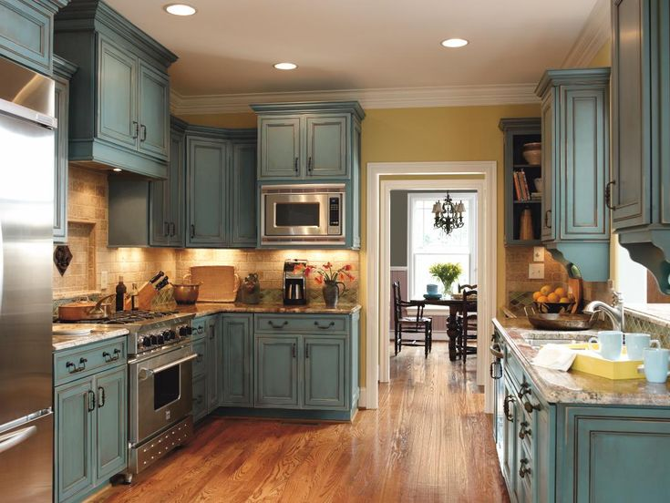 Turquoise Rust Kitchen Cabinets in Maple from Decora Cabinetry against oak floors and stainless appliances. http://www.decoracabinets.com/