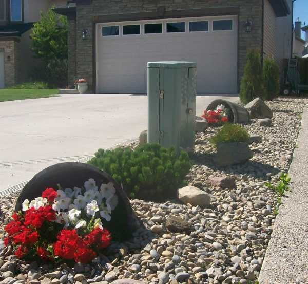 Drawing the eye away from a utility box can be more effective than trying to hide it. These attractive rain barrels do just that. The river rock makes for a great drainage bed collecting the downspout water from between the homes in times of heavy rain.