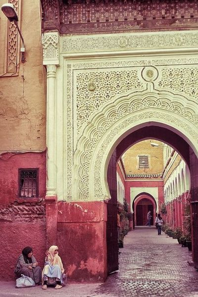Marrekech streets in Morocco. Love the architecture and the arched walkways and the red walls.